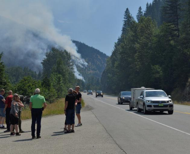 Tourists from Denmark stop to photograph one of several wildfires burning near Little Fort, Canada. Photo: Reuters