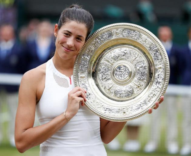 Spain's Garbine Muguruza poses with the trophy as she celebrates winning the final against Venus Williams