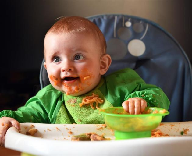 Eight month-old Hank Chapman makes a mess of his spaghetti and toast yesterday. PHOTO: STEPHEN...
