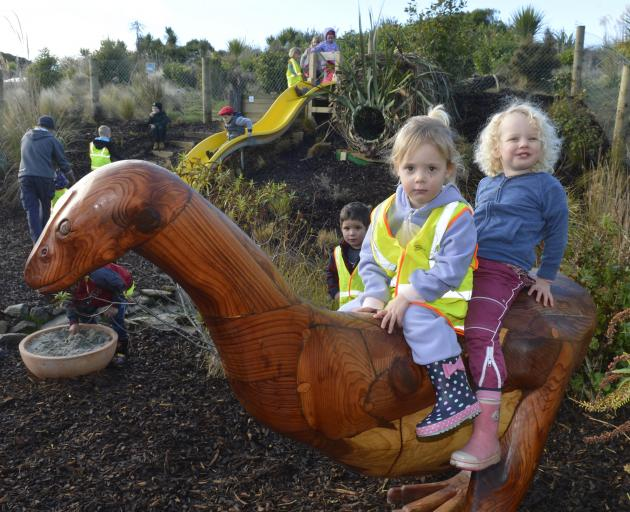 Niamh White (2, left) and Mica Nye (3) were first on a carved moa when the Orokonui Ecosanctuary opened its nature play area yesterday. Photo: Gerard O'Brien