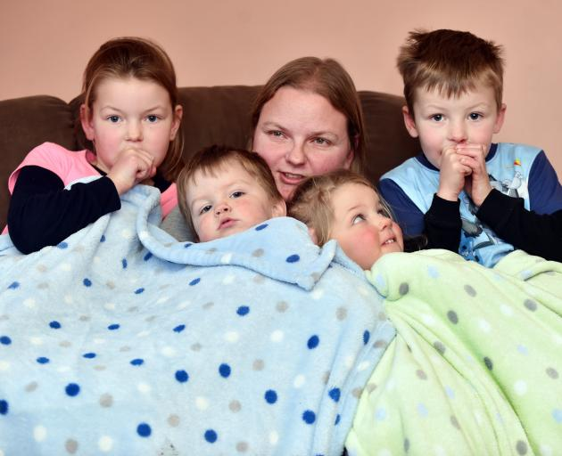 The Ferguson family attempting to keep warm in their Mosgiel home yesterday are (from left) Emily...