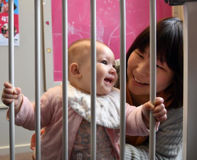 Madoka Yamauchi and her daughter Mia McKenzie behind a safety gate given to the family by Plunket...