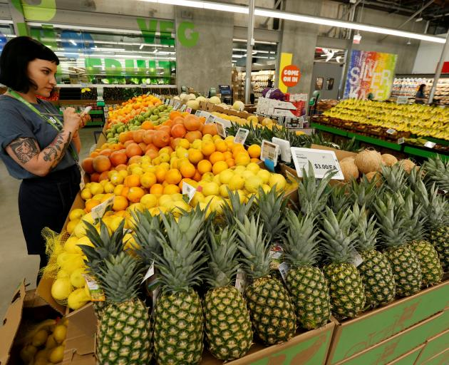 An employee checks the prices of lemons at a Whole Foods store. The US Whole Foods chain was...