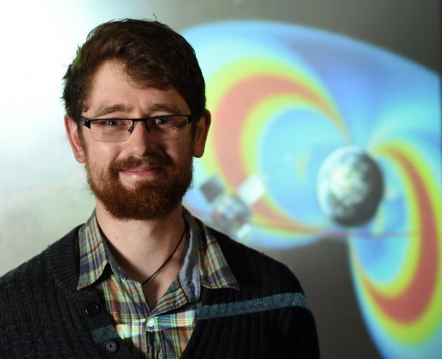Aaron Hendry in front of an artist's impression of Earth's invisible radiation belts and one of...