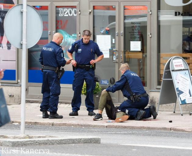 The suspect lies on the ground surrounded by police officers at the Market Square where several people were stabbed, in Turku, Finland. Photo: Reauters via Kirsi Kanerva