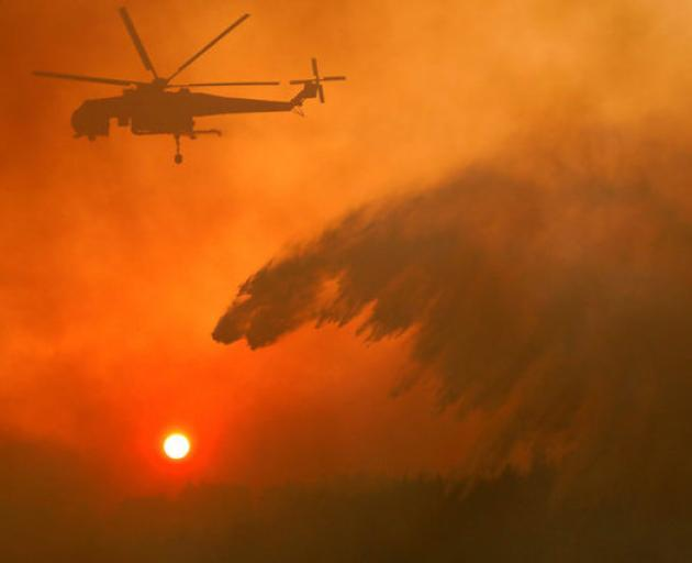 A firefighting helicopter makes water drop as a wildfire burns near the village of Metochi. Photo: Reuters