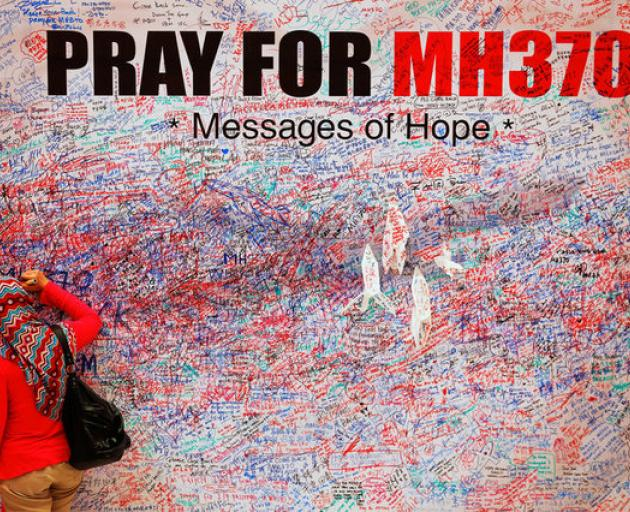 A woman leaves message of support and hope for passengers of missing Malaysia Airlines MH370 in central Kuala Lumpur. Photo: Reuters