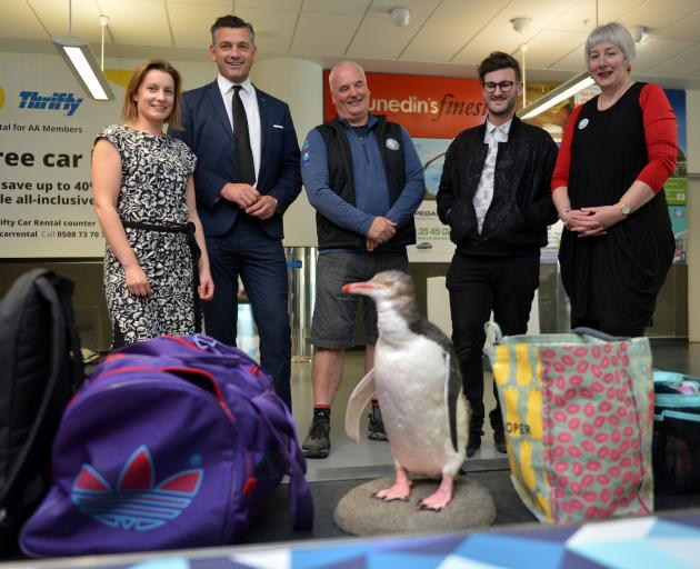 """A """"visitor'' makes an appearance on the Dunedin Airport baggage carousel watched by (from left)..."""