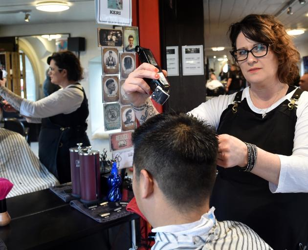 Bloke customer Harry Huang gets his hair cut by owner Keri O'Connor, without a drink in hand. Photo: Peter McIntosh