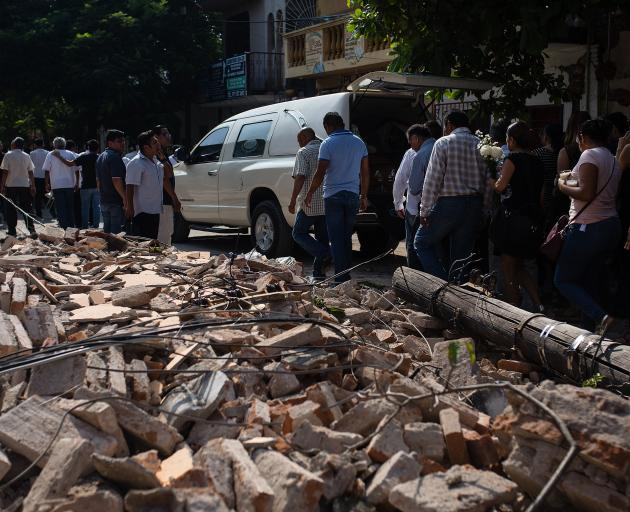 People walk by debris during a funeral ceremony held for a person that died in the earthquake in Juchitan, Mexico. Photo:Getty Images