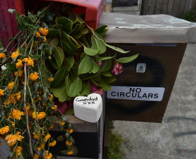 Flowers and tributes sit on the letterbox of the Nutsford St flat where a man's body was discovered during a house fire about midnight on Friday. Photo: Gregor Richardson