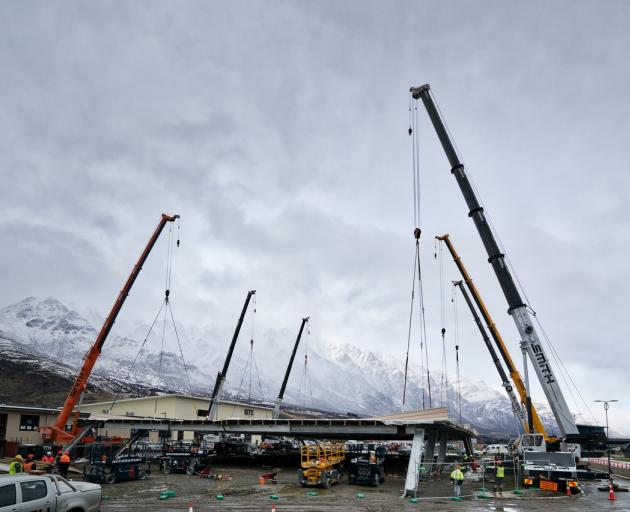 A commercial building's 80-tonne steel roof was lifted in place by six cranes at Queenstown's...