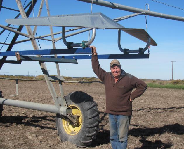 Greg Lovett stands under the irrigator stabilising wing. Photo: Maureen Bishop