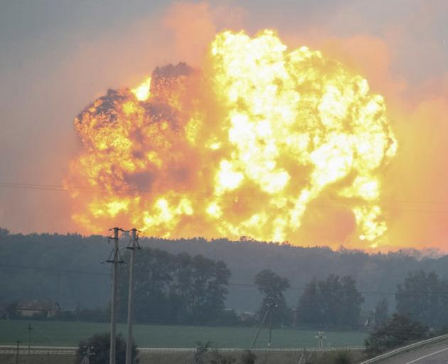 Smoke and flames rise over a warehouse storing ammunition for multiple rocket launcher systems at a military base in the town of Kalynivka. Photo: Reuters