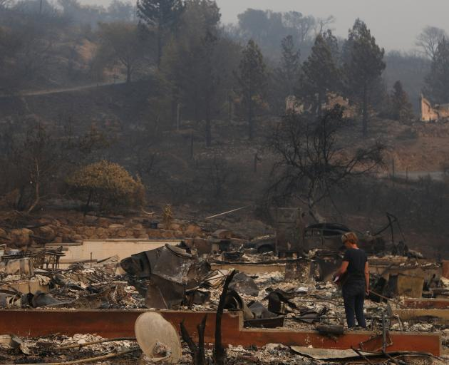 A woman surveys the remains of a home destroyed by wildfire in Napa. Photo: Reuters