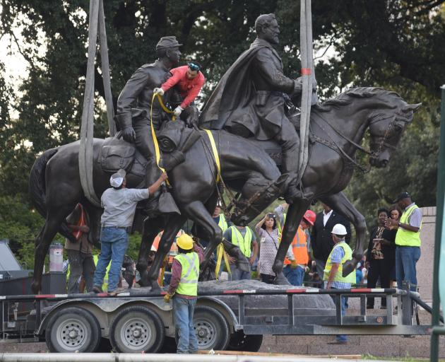 Workers remove the statue of Confederate general Robert E. Lee in Dallas, Texas, last month. Photo: Reuters