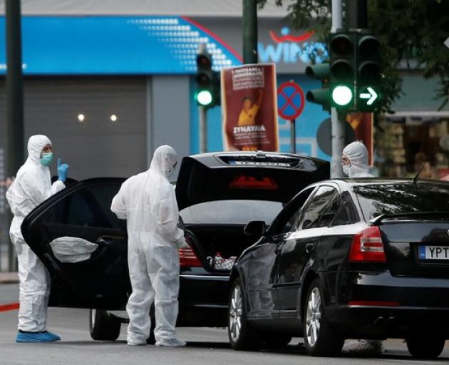 Forensics officers inspect the car of former Greek prime minister and former central bank chief Lucas Papademos following the detonation of an envelope injuring him and his driver, in Athens. Photo: Reuters