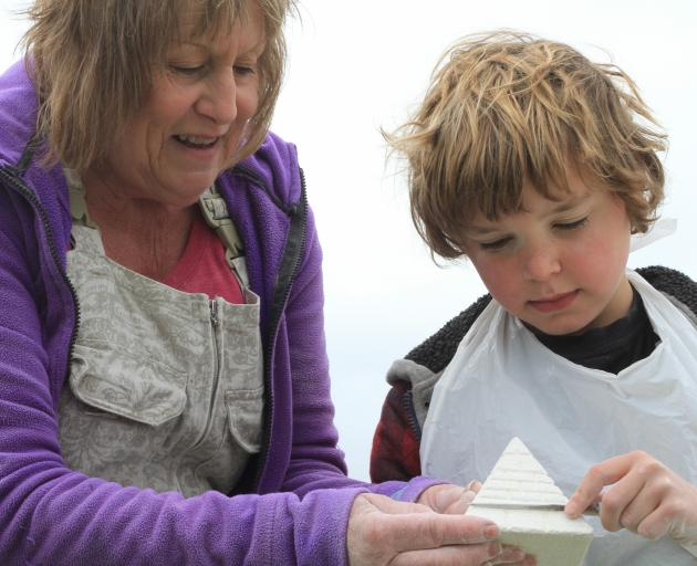 Linda Wilson, of Weston, shows Arthur Gillespie (9), of Nelson, how to carve his pyramid. Arthur...