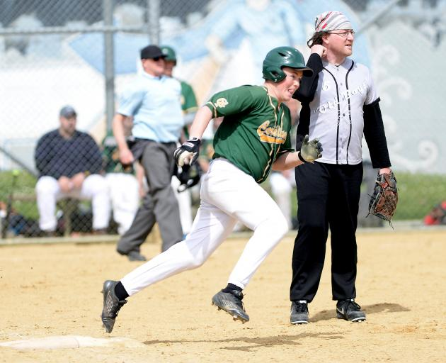 William Hewett, of Cardinals, rounds first base as Old Boys fielder Reece Flawn looks on at Otago...