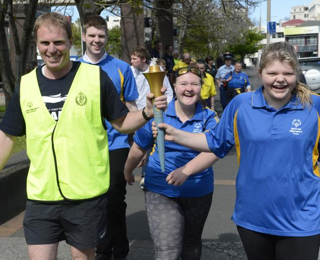Senior Sergeant James Ure and Britney Kerr carry the Special Olympics Flame of Hope through central Dunedin yesterday as Special Olympians Keaton Bryant and Debbie Kennedy watch. Photo: Gerard O'Brien