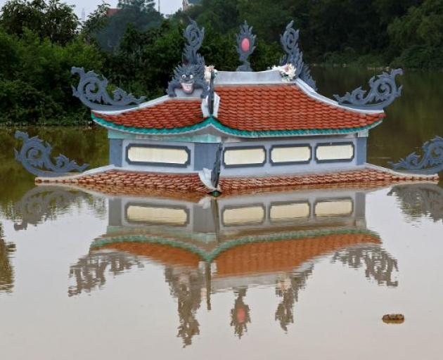 A submerged temple is seen in a flooded village after a tropical depression in Hanoi. Photo: Reuters