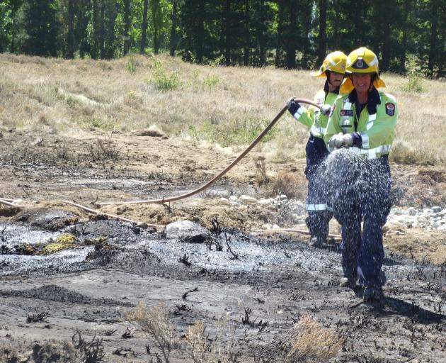 Firefighters douse a small scrub fire near Alexandra this afternoon. Photo: Tom Kitchin