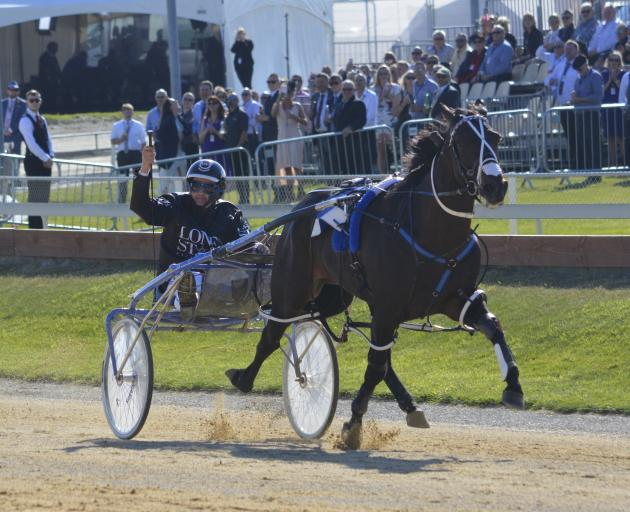 Never in doubt ... Co-trainer and driver Mark Purdon salutes the crowd after driving champion...