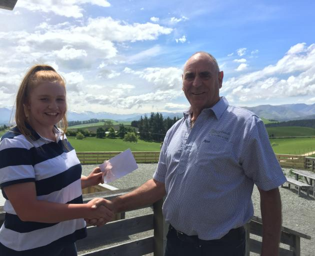 Briar Swanson is congratulated by South Canterbury North Otago Deer Farmers Trust member Keith Orange (right) after the trust provided her with financial assistance to go towards her time as a cadet at Coleridge Downs Training Farm. Photo: Supplied