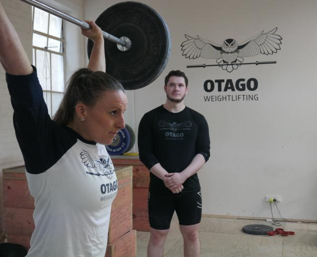 Dunedin weightlifter Amanda Gould trains at the club on Tuesday night,  watched by coach Callan