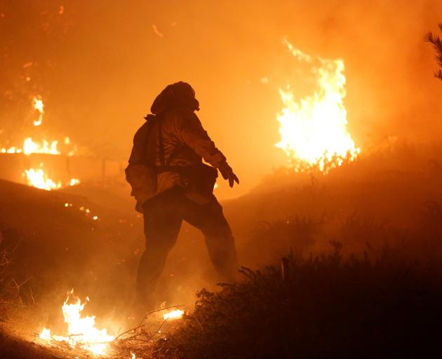 A firefighter stomps out small embers on a ranch during the Creek Fire in the San Fernando Valley...