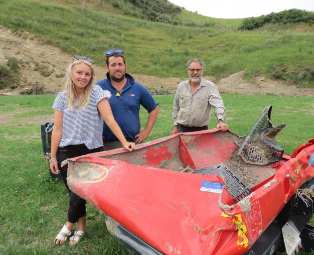 Farmers Chris Pemberton (centre), his father Rod Pemberton and his partner Jaimee Coulter, have had a busy couple of weeks cleaning up the Tima Burn Rd farm after a flash flood on November 26. Their near-new fertiliser spreader was found kilometres away i