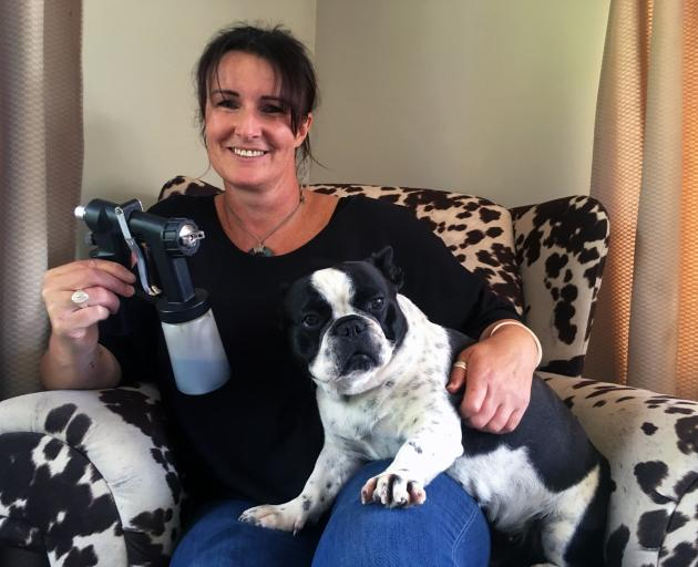 Primed Spray Tanning owner and operator Carmen Copland holds her spraygun and French bulldog Jiggy at her home in Kenmure, where she operates her spray tanning business. PHOTO: SHAWN MCAVINUE
