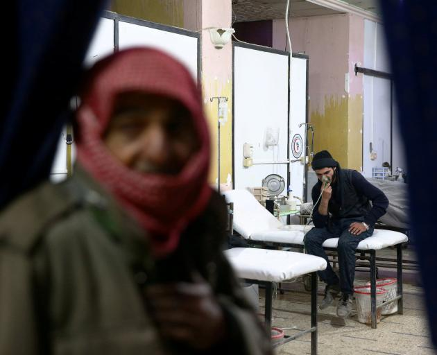 A man breathes through an oxygen mask at a medical centre in Ghouta province, the site of the...