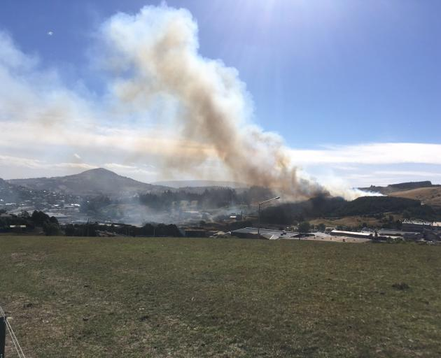 A fire is burning on a hill behind the old Burnside freezing works. Photo: Peter McIntosh