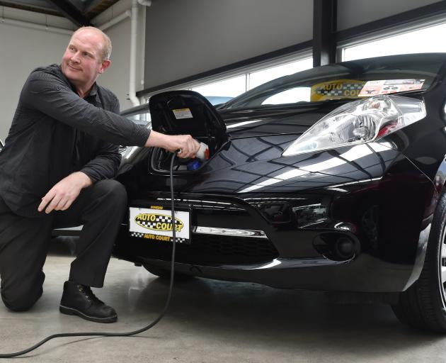 Auto Court manager Nelson Cottle demonstrates how to charge one of the two Nissan Leaf electric vehicles in the yard. Photo: Gregor Richardson