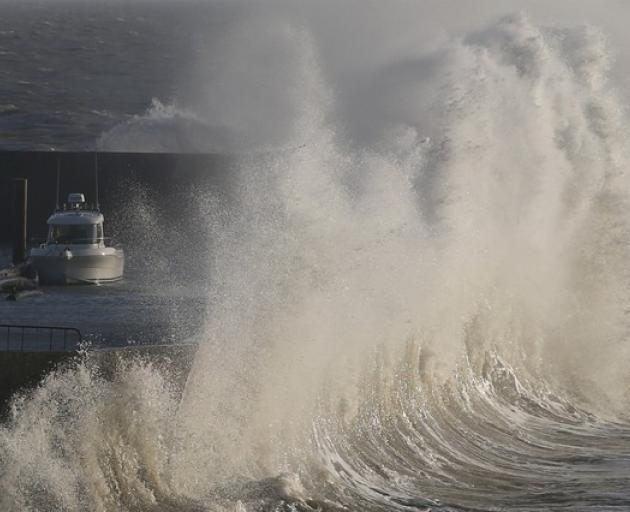 A high wave crashes on the protecting wall at the fishing harbour in Pornic. Photo: Reuters
