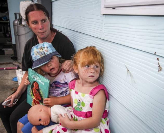 Tracey Hibbs was glad her daughter, Ella-Rose, 6 (middle), and friend, Leeanah-Rose, 4, weren't outside when a wanted man fled through her property, leaving a blood trail, and stains, including this bloodstain on neighbour Zoe Gifkins' house. Photo: Paul