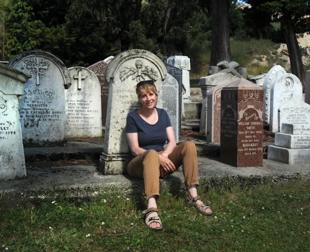 New Kaitangata resident Denise Dent sits in front of headstones at the local cemetery, including those for miners killed on February 21, 1879. Photo: Christine O'Connor