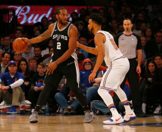 Spurs forward Kawhi Leonard handles the ball as he is guarded by Knicks guard Courtney Lee
