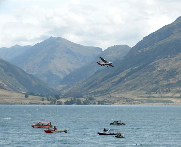 Planes, boats and jet skis search for the missing skydiver in Lake Wakatipu yesterday. Photo:...