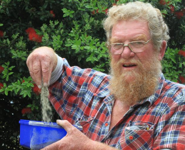 Mark Brady, of Moeraki, shows some of the ''dust'' containing the ashes of rabbit skins made at...