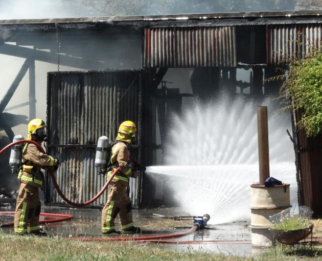 Firefighters dampen down a fire that took hold in the workshop of this Arthurs Point home yesterday. Photo: Guy Williams