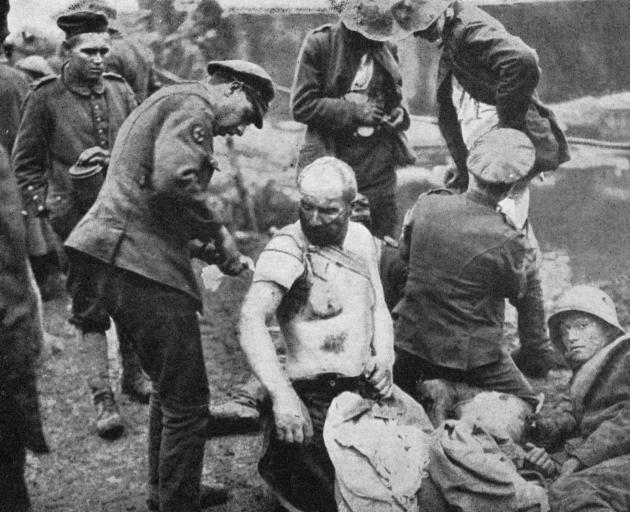 The battle of Broodseynde: R.A.M.C. men dressing wounds for prisoners, who are treated similarly to our own men. - Otago Witness, 9.1.1918.