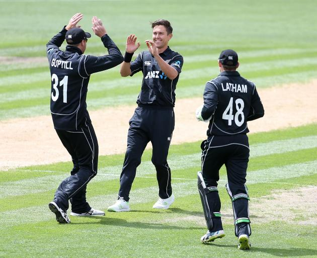 Martin Guptill Trent Boult and Tom Latham of New Zealand celebrate the dismissal of Fakhar Zaman