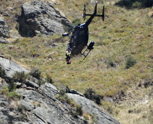 A paramedic is about to be winched from the Otago Regional Rescue helicoper down to the site of a paraglider crash on Roys Peak yesterday. Photo: Kerrie Waterworth
