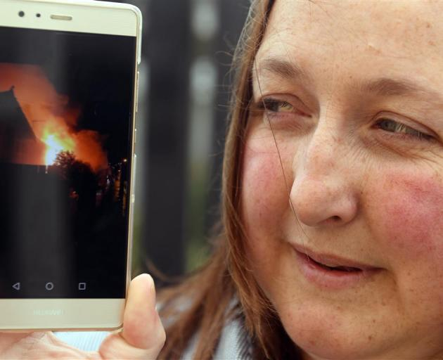 Mel Ryall displays a photo she took after rescuing an elderly man from a  Wesley St house fire...