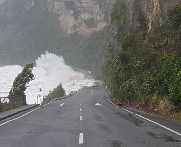 Waves lap over State Highway 6 at Punakaiki. Photo: Martijn van der Maarel via NZ Herald