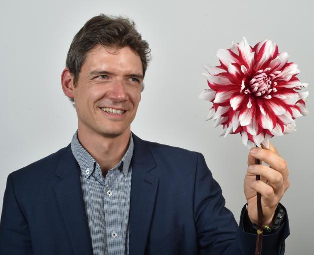Diabetes researcher Dr Alex Tups holds a dahlia which could hold the key to diabetes prevention....