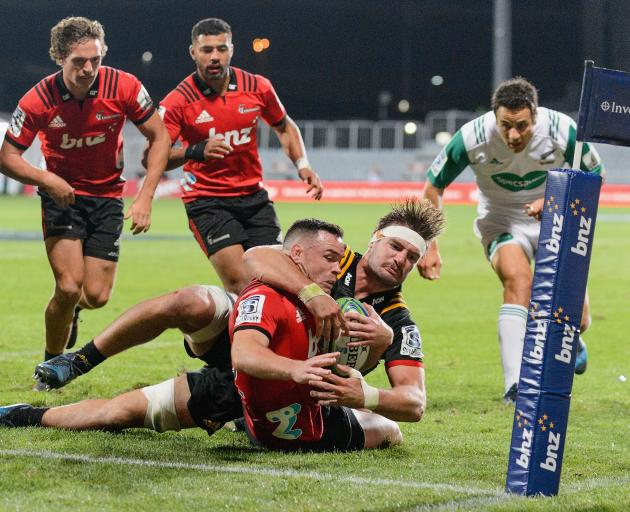 Ryan Crotty, of the Crusaders, is tackled by Lachlan Boshier, of the Chiefs, during the round two...
