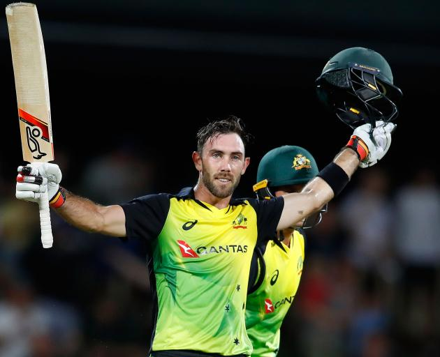 Glenn Maxwell of Australia celebrates his century after hitting a six from the last ball during...
